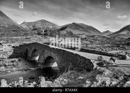 B&W image - The old stone bridge over the Sligachan River with a backdrop of the Cuillin Hills, Isle of Skye, Highland Region, Scotland, UK - Stock Image