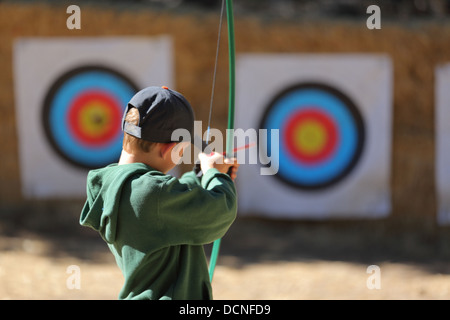 Young boy pointing arrow at target - Stock Image