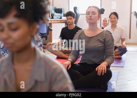 Serene creative businesswoman meditating in office - Stock Image