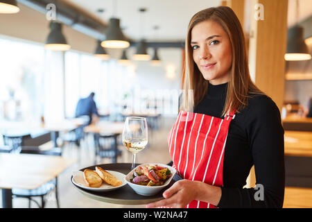 Young woman with tray makes training to waitress in the restaurant - Stock Image