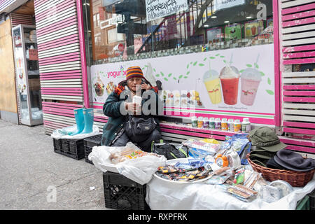 A street scene in Jackson Heights Queens, New York featuring a women selling knick knacks & clothing while talking on her cell phone. On 82nd Street. - Stock Image