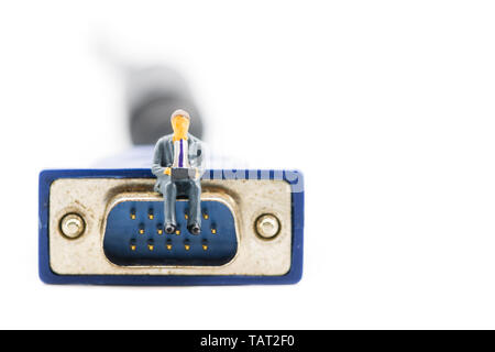 Macro shot on miniature figure as business man working on the laptop notebook sitting on video VGA plug, isolated on white background. Information tec - Stock Image