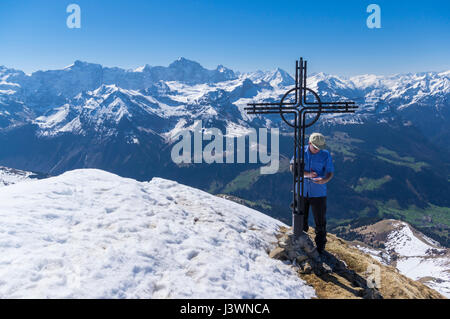 Male hiker standing next to a cross on the summit of Rossstock (2461m) in spring, writing his name into the summit - Stock Image