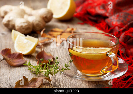 autumn tea with ginger, lemon and thyme on old wooden background - Stock Image