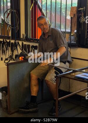 A glassblower giving a demonstration. - Stock Image