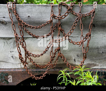Old worn rusty tire chains for traction in snow and ice hanging on the wooden side on a truck in the Adirondack Mountains, NY USA - Stock Image