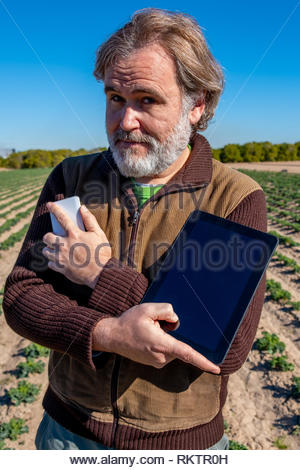 A farmer with a tablet in one hand and a mobile phone in the other poses in his field. - Stock Image