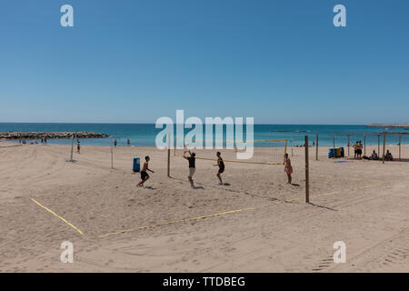 Four boys playing hand ball on the beach - Stock Image