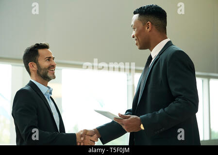 Businessmen shaking hands in office lobby - Stock Image