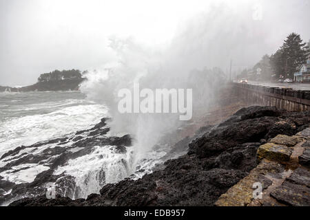 Waves crash on the rocky Pacific shoreline and seawall, washing over U.S. Route 101 and passing cars in Depoe Bay, - Stock Image