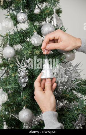 Man Decorating Christmas Tree - Stock Image