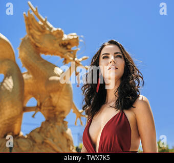 Pretty brunette woman posing with a golden dragon in the background - Stock Image