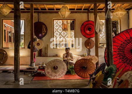 A woman crafts a handmade umbrella at her shop on Inle lake, Myanmar. - Stock Image