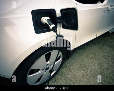Electric car being charged at a charging station - Stock Image