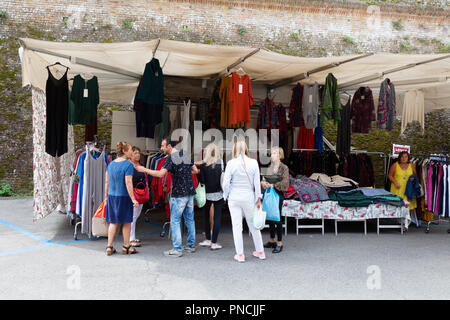 People shopping for clothes in Siena Market, Siena, Tuscany Italy Europe - Stock Image