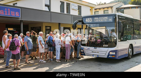 GARDA, LAKE GARDA, ITALY - SEPTEMBER 2018: Large crowd of people waiting to get on a bus in the bus station in the town of Garda on Lake Garda. - Stock Image