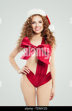 Sexy fashion model woman in silky swimsuit and Santa hat on white, Christmas or New Year gift concept - Stock Image