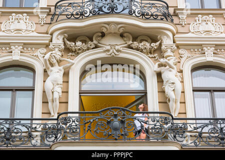 Riga art nouveau architecture, a young woman on a balcony in Elizabetes Iela in the Art Nouveau district of Riga looks up at one of two caryatids. - Stock Image
