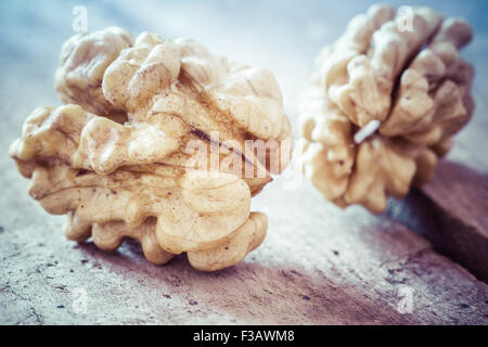 Walnuts on a wooden table in retro style. - Stock Image