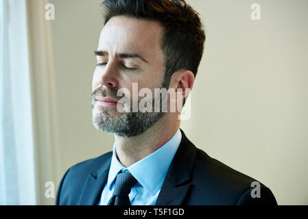 Thoughtful businessman standing in hotel - Stock Image