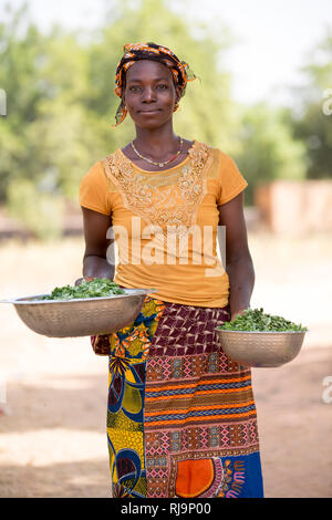 Kisambo Village, Yako, Burkina Faso, 28th November 2016;  Miriam Ouedraogo, cooking a meal for 10, includes moringa leaves just picked from the village garden as a main ingredient. - Stock Image