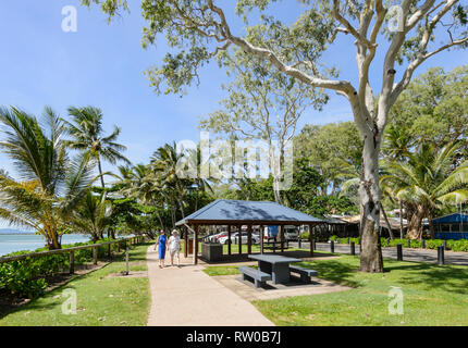 Couple walking along the esplanade at Palm Cove, Cairns Northern Beaches, Far North Queensland, QLD, FNQ, Australia - Stock Image