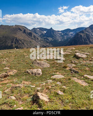 Sunny Colorado Rockies, with dominant rock field in front, dramatic  blue-grey mountains behind, and bright blue sky above, with puffy clouds. - Stock Image
