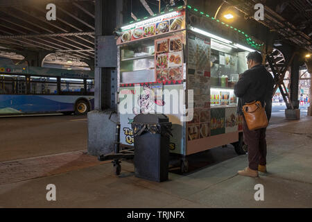 On his way home from work, a man buys fast food from a Mexican food cart under the el in Woodside, Queens, New York. - Stock Image