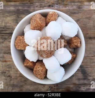 Looking down from above onto a bowl full of brown and white sugar cubes in a square Instagram style frame - Stock Image