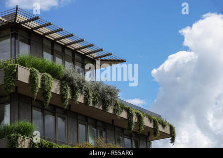 modern building that houses numerous trees and plants in the balconies - Stock Image