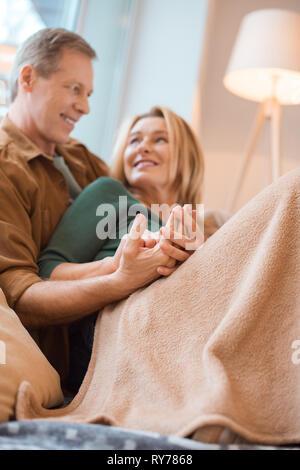 selective focus of happy couple resting under soft fleece blanket - Stock Image