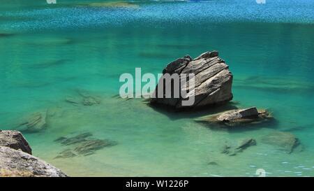 Rock and turquoise water of Lake Cauma. - Stock Image