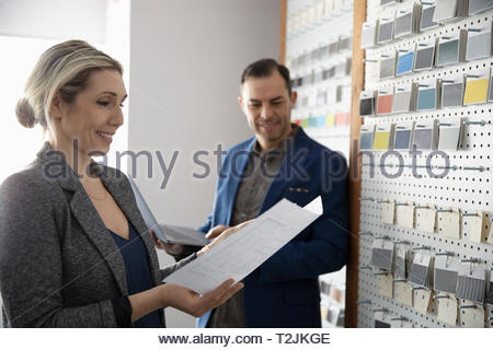 Interior designers reviewing blueprint in design studio - Stock Image