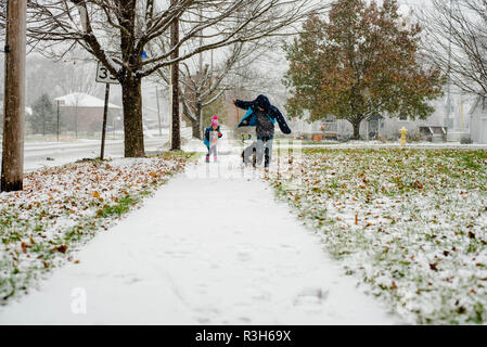 two children play in the snow during the winter in pennsylvania, USA - Stock Image