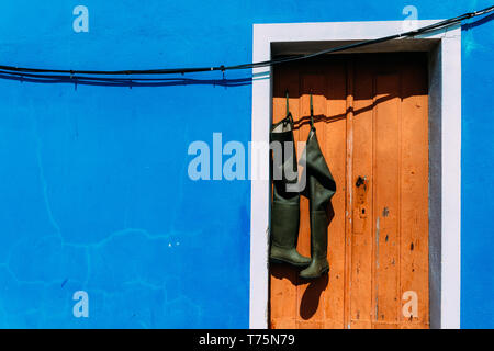 Pair of wellies boots hanging from brown rustic doorway with bright blue wall facade copy space. - Stock Image
