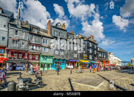 Tourists enjoy a sunny day on the Normandy Coast of France at the picturesque village of Honfleur France with slate - Stock Image
