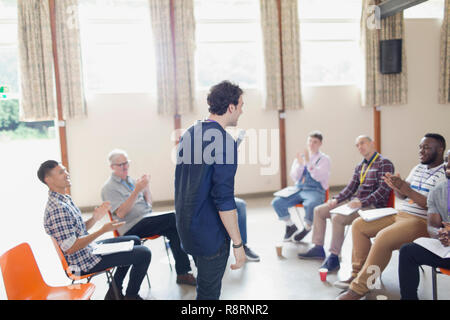 Man with microphone speaking to group in community center - Stock Image