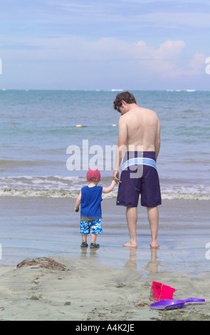 Father and son looking out on the Atlantic ocean from a Puerto Rican beach. - Stock Image