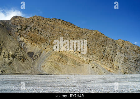 Rocky hill with visible geological stratas overhanging the dry riverbed of the Kali Gandaki between Jomsom and Kagbeni, Upper Mustang region, Nepal. - Stock Image
