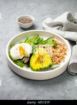 healthy diet breakfast. quinoa, avocado, asparagus, poached egg  in a white ceramic plate on a gray stone background - Stock Image