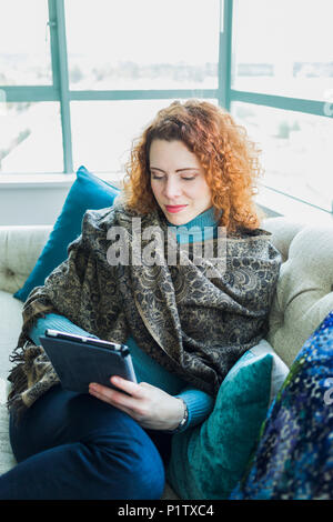 Portrait of a woman sitting with a laptop by a window; Surrey, British Columbia, Canada - Stock Image