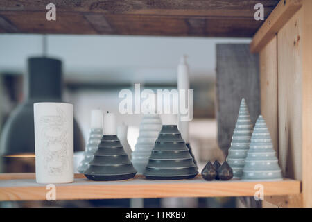 Close-up of potteries on wooden shelf at workshop - Stock Image