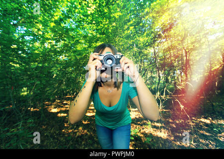 Young woman in forest with a camera. - Stock Image