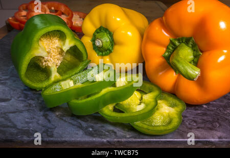 Food preparation: Three fresh uncooked peppers on a granite chopping board, one of them sliced. - Stock Image