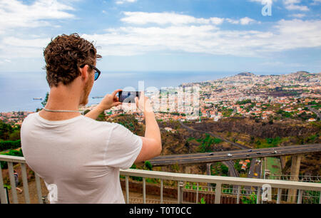 Young man tourist taking a picture of city of Funchal on Madeira island Portugal, on summer day. - Stock Image