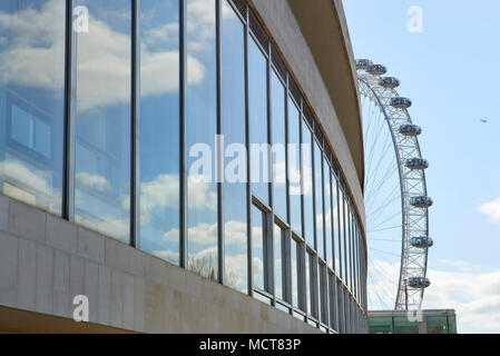 London Eye in the far background, with view obstructed by large glass windows of Royal Festival Hall in the foreground. - Stock Image