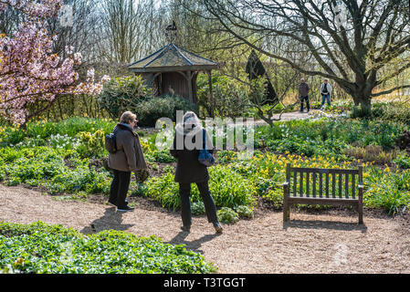 People admiring the spring flowers overlooking the lower pond, with gazebo in the background. - Stock Image