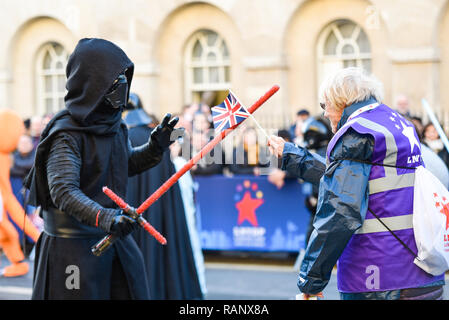 Kylo Ren costume of fictional character in the Star Wars films at London's New Year's Day Parade, UK. Light sabre sword fighting with lnydp marshal - Stock Image