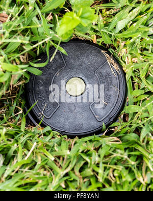 A Rainbird in-ground sprinkler head in a fescue lawn in Kansas, USA. - Stock Image