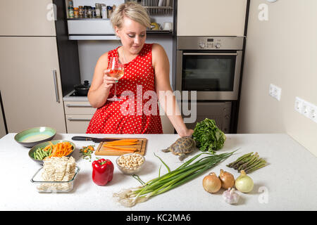 Woman observes tortoise eating on salad - Stock Image